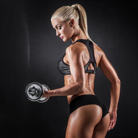 Foto de Brutal athletic woman pumping up muscles with dumbbells - Imagen libre de derechos