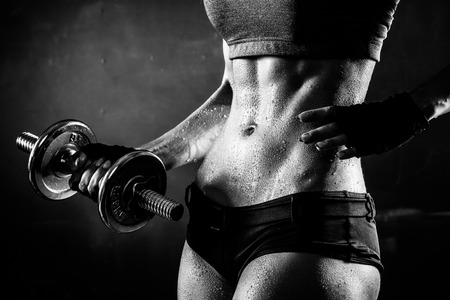 Brutal athletic woman pumping up muscles with dumbbells in monochrome