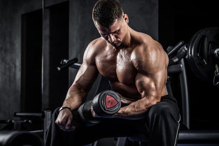Foto de Brutal athletic man pumping up muscles with dumbbells - Imagen libre de derechos