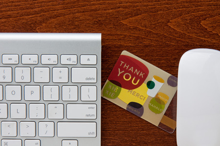 Thank you gift card in between keyboard and mouse on a brown wooden grain desktop