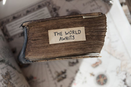 Foto de Traveler idea. The World Awaits text, old book and old geographic map - Imagen libre de derechos