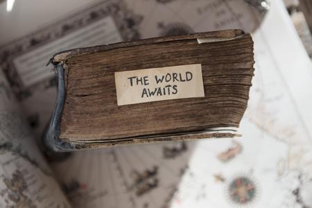 Foto de Traveler idea. The World Awaits text, old book and old geographic map - Imagen libre de derechos