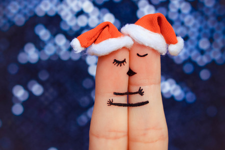 Finger art of a Happy couple. Couple kissing and hugging in the new year hats.