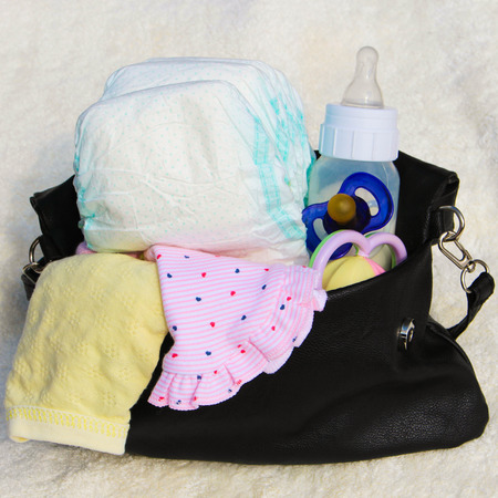 Photo for Womens handbag with items to care for the child - Royalty Free Image