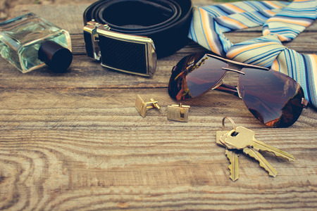 Photo for Men accessories: sunglasses, tie, cufflinks, strap, keys, perfume on the old wood background. Toned image. - Royalty Free Image