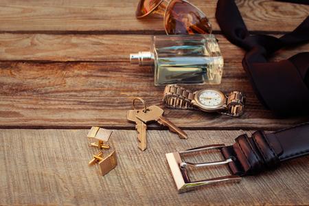 Photo pour Men accessories: sunglasses, bag, wrist watch, cufflinks, comb, strap, keys, tie, perfume on the old wood background. Toned image. - image libre de droit