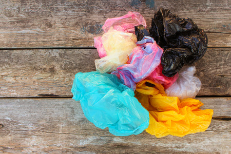Foto de Different plastic bags on old wooden background. Top view. - Imagen libre de derechos