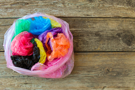 Foto de Different plastic bags on wooden background. - Imagen libre de derechos