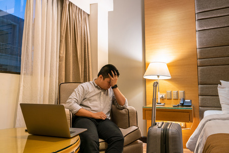 Photo pour Young businessman feels tired and frustrated with work in the business trip - image libre de droit