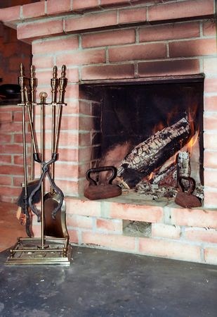 Fireplace with two old irons in it and fire irons