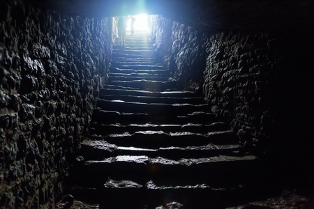 Photo pour Underground passage under old medieval fortress. Old stone stairs to exit of tunnel. - image libre de droit