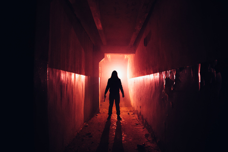 Photo pour Creepy silhouette with knife in the dark red illuminated abandoned building. Horror about maniac concept. - image libre de droit