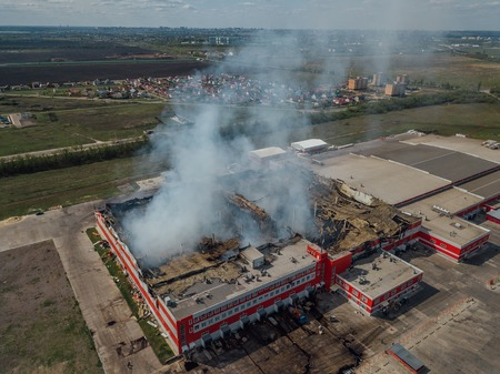 Photo for Burning industrial distribution warehouse, aerial drone view - Royalty Free Image