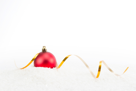 Foto de Red ball Christmas decoration with gold ribbon on snow isolated on white background. Space for your text. - Imagen libre de derechos