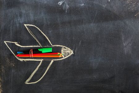 Photo pour Back to school. Chalked drawing of an airplane on a school blackboard with school supplies and an empty place for your text or design. - image libre de droit