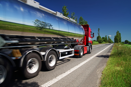Photo pour Mirroring the landscape chrome tank truck moving on a highway, view from eye level - image libre de droit