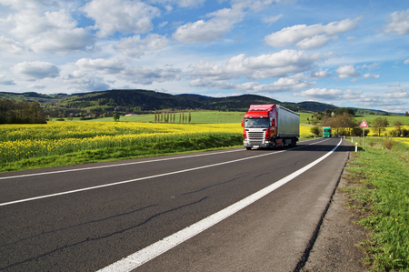 Photo pour Red and green trucks arrives on an asphalt road between the yellow flowering rapeseed field in the rural landscape. Wooded mountains in the background. Blue sky with white clouds. - image libre de droit