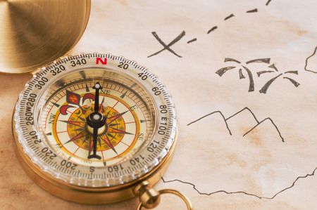 Photo pour Closeup of compass over stained yellowed paper sheet with part of schematic hand drawn treasure map - image libre de droit