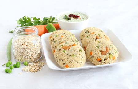 Photo for Oats Idli or cake, a healthy Indian vegetarian food, with vegetables like carrot, peas, green beans and capsicum, and cashew nuts, which is steam cooked. - Royalty Free Image
