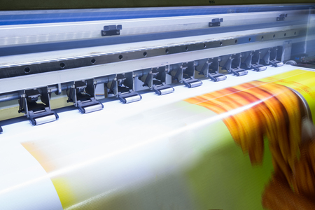 Foto de Format large inkjet printer working on yellow vinyl banner - Imagen libre de derechos