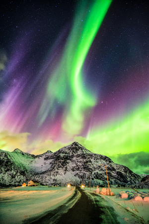 Photo pour Aurora Borealis (Northern lights) explosion over mountains and rural road at Skagsanden beach, Lofoten island, Norway - image libre de droit
