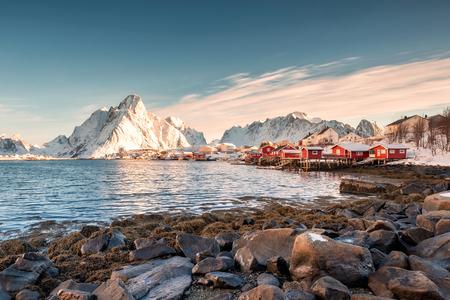 Photo pour Scandinavian fishing village with snowy mountain at coastline. Reine, Lofoten islands, Norway - image libre de droit