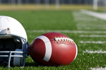 Foto de American Football and Helmet on the Field with room for copy - Imagen libre de derechos