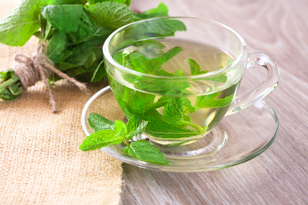 Photo for Cup of mint tea and a bunch of mint on the table - Royalty Free Image