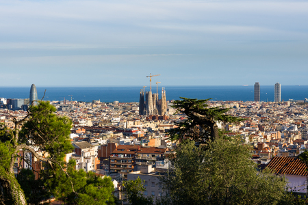 Foto de View of the roofs of Barcelona from Parc Guell terrace. La Sagrada Familia on the side and the sea on the background. Barcelona, Spain. - Imagen libre de derechos