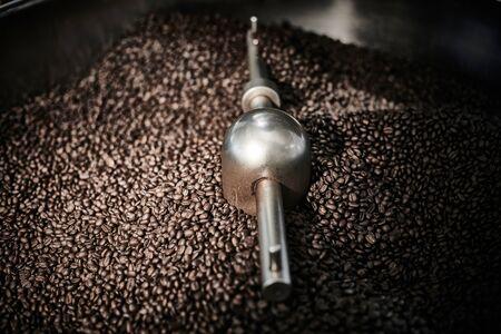 Foto de Freshly roasted coffee beans in a coffee roaster.Frozen moment. - Imagen libre de derechos