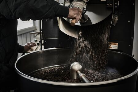 Foto de Freshly roasted coffee beans pouring from a large coffee roaster into the cooling cylinder. - Imagen libre de derechos