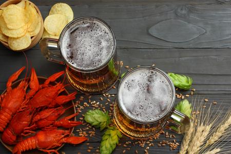 Foto de Glass beer with crawfish, hop cones and wheat ears on dark wooden background. Beer brewery concept. Beer background. top view with copy space - Imagen libre de derechos