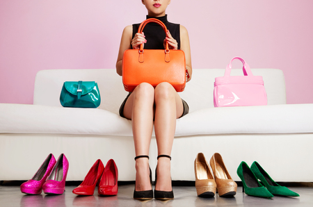 Photo pour Colorful shoes and bags with woman sitting on the sofa. - image libre de droit