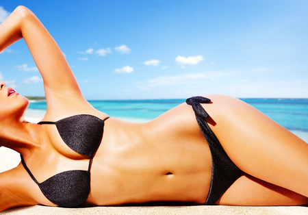 Foto de Woman with black bikini on the beach. Beautiful tanned skin. - Imagen libre de derechos