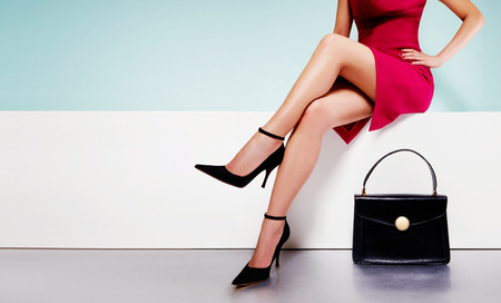 Foto de Beautiful legs woman wearing red dress with black purse hand bag with high heels shoes sitting on the white bench. with copyspace. - Imagen libre de derechos
