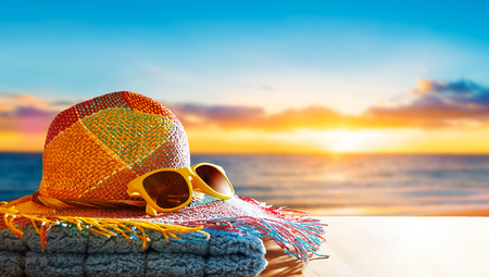Photo pour Summer vacation beach side image. A colorful straw hat, a yellow sunglasses and a towel on the wooden table. Copy space for your text on the table and sky. - image libre de droit