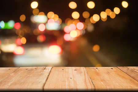 Blank wooden table on front abstract background of traffic jam, bokeh light