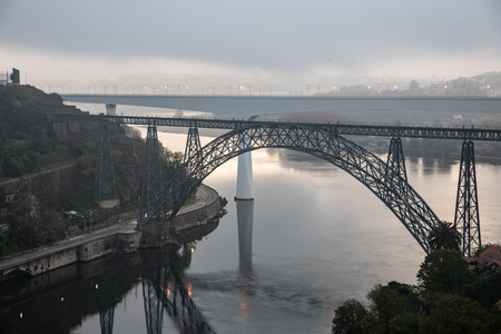 Photo pour Distant view of the D. Maria Pia and Sao Joao Bridges, in Porto, Portugal during the morning hour. Cloudy sky. - image libre de droit