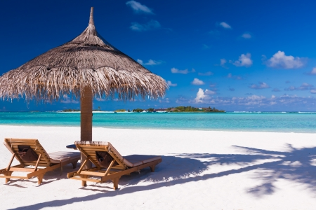 Foto de Two chairs and umbrella on a beach with shadow from palm tree - Imagen libre de derechos