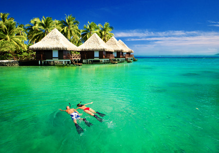 Photo for Couple snorkling in tropical lagoon with over water bungalows - Royalty Free Image
