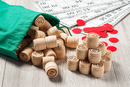 Foto de Board game lotto. Stacked wooden lotto barrels with bag, game cards and red chips for a game in lotto on the background - Imagen libre de derechos