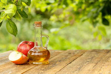Photo pour Apple vinegar in glass bottle with cork and fresh red apples on old wooden boards with blurred green natural background - image libre de droit