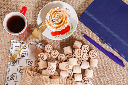 Photo pour Wooden lotto barrels in pouch and game cards for a game in lotto with notebook, pen, cup of coffee, fork and homemade biscuit in the form of rose on white saucer. Top view. - image libre de droit