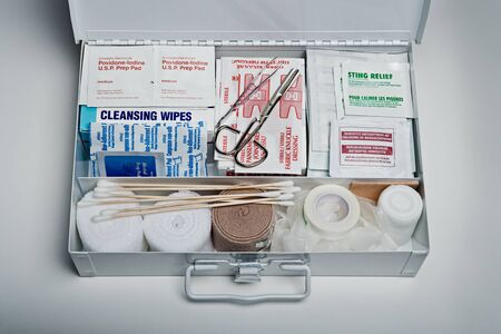 Foto de Organized first aid kit packed with emergency medical supplies on grey background - Imagen libre de derechos