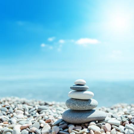 Photo pour zen-like stones on beach and sun in sky. soft focus on bottom - image libre de droit
