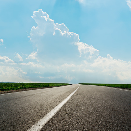 Photo pour asphalt road with white line and clouds in blue sky - image libre de droit