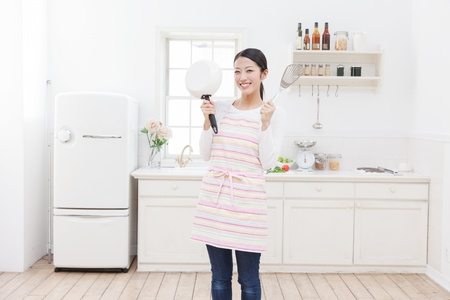 Young Asian woman with cooking utensils in the kitchen
