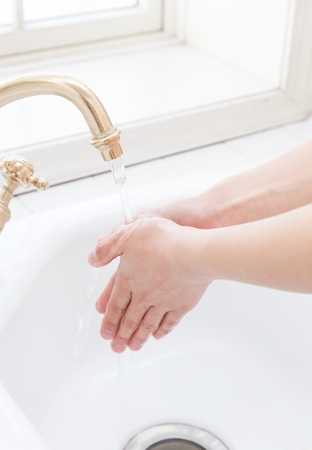 Hand-washing sink in the hands of a woman by the window