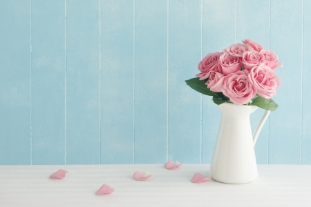 Photo for Rose placed on the desk in blue background - Royalty Free Image