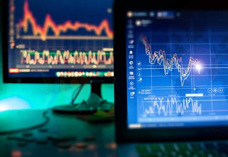 Foto de Day trader screen with graphs and charts in dark - Imagen libre de derechos